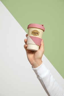 Front view of hand holding coffee cup