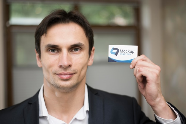 Front view of handsome businessman holding business card