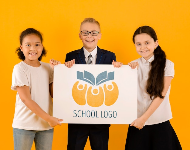 Front view happy kids holding mock-up sign