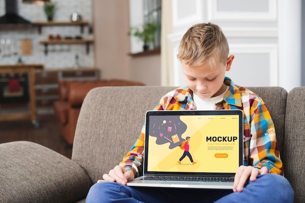 Front view of kid on couch holding laptop