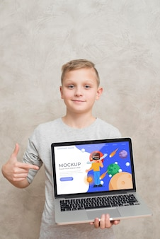 Front view of kid holding and pointing at laptop