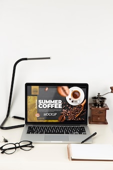 Front view of laptop on desk with lamp and glasses