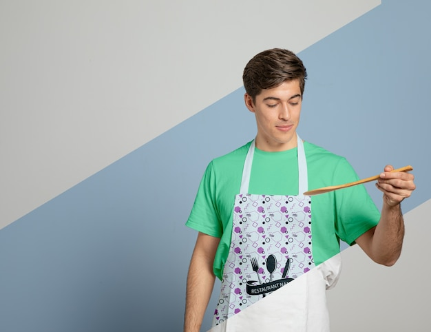 Front view of man in apron holding wooden spoon