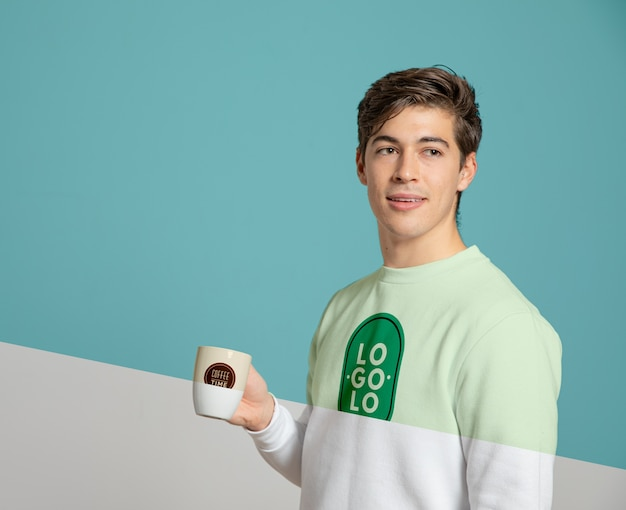 Front view of man in sweater holding mug