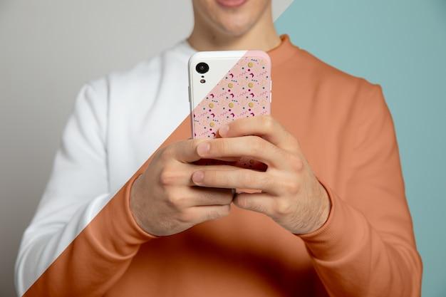 Vista frontale dell'uomo che per mezzo di uno smartphone