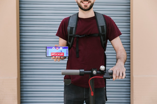 Человек с самокатом, держащий мобильный макет