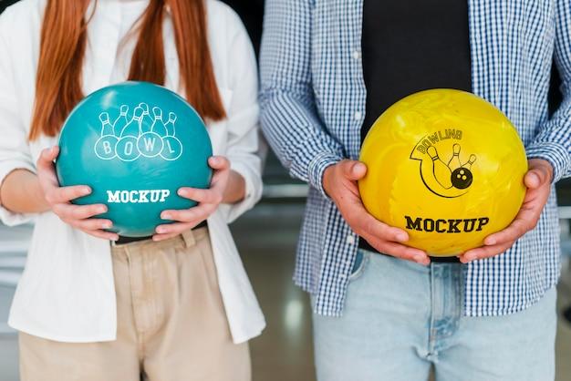 Vista frontale dell'uomo e della donna che tengono le palle da bowling