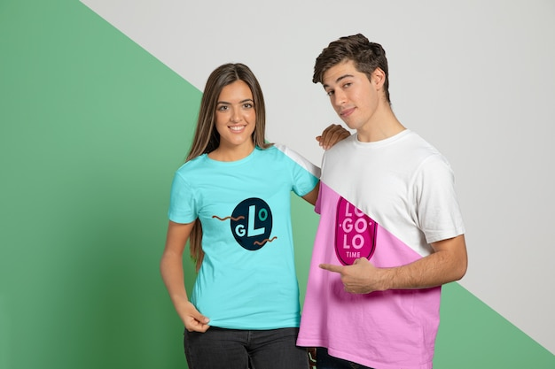 Front view of man and woman posing in t-shirts and pointing at them