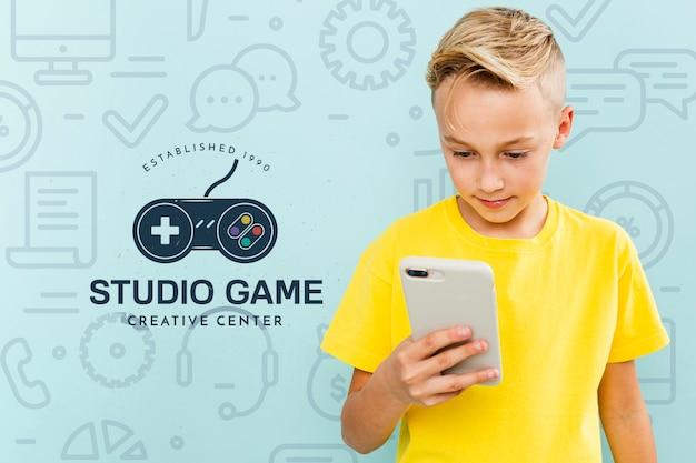 Вид спереди мальчика, плененного смартфоном
