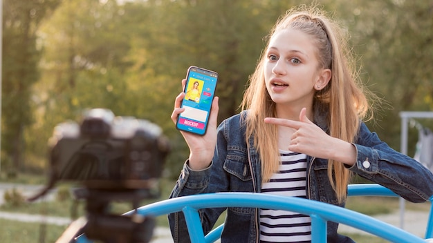 Детский видеоблогер со смартфоном на открытом воздухе, вид спереди