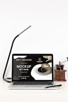 ノートパソコンとランプのあるデスク表面の正面図