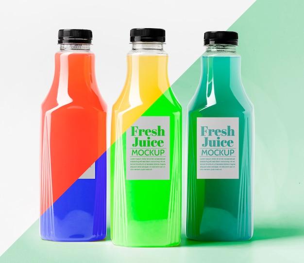 Вид спереди различных прозрачных бутылок сока с крышками