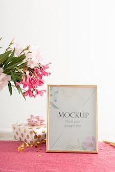 Вид спереди элегантной рамки дня рождения с подарком и цветами