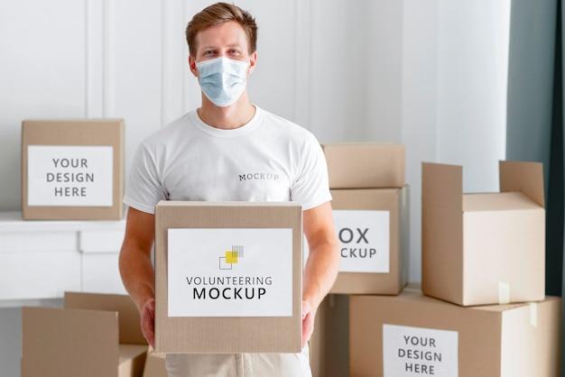 Вид спереди мужского добровольца с медицинской маской, держащего коробку для пожертвований еды