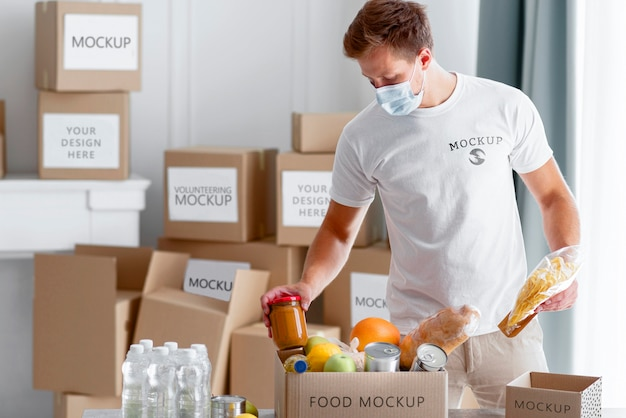 Вид спереди мужского добровольца с медицинской маской, готовящего коробку для пожертвований еды