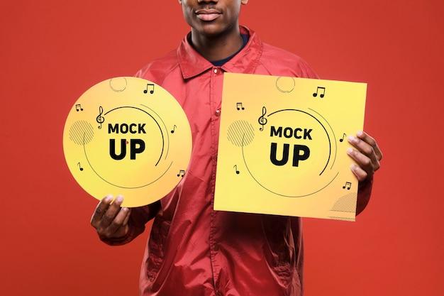 Вид спереди человека, держащего виниловый диск для макета музыкального магазина