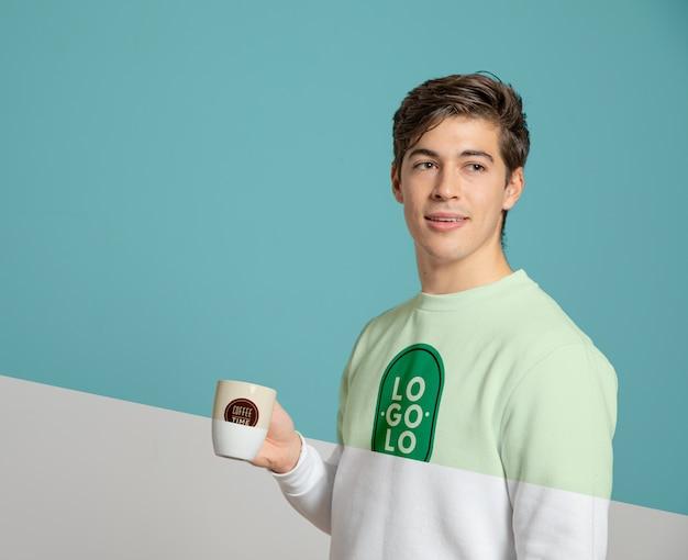 Вид спереди человека в свитере, держащего кружку