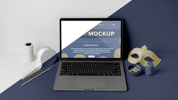 노트북과 마스크가있는 최소한의 카니발 모형의 전면보기