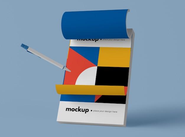 Вид спереди ручки и блокнота с геометрическими фигурами
