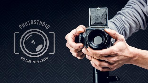 Вид спереди фотографа, регулирующего камеру