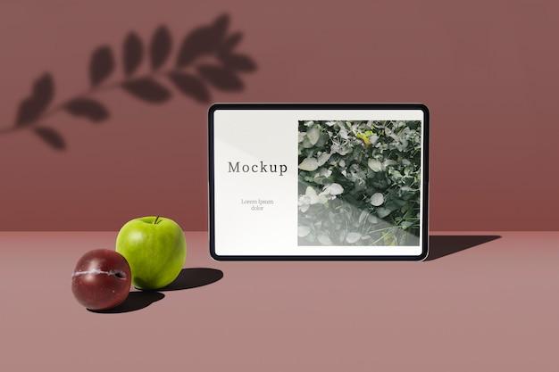 Вид спереди планшета с яблоком и сливой