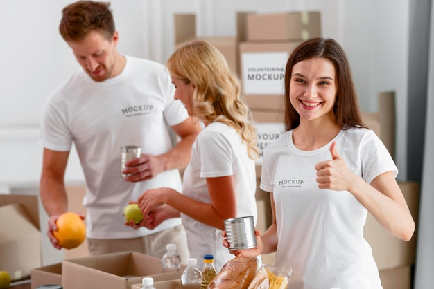 Вид спереди добровольцев, держащих продукты для пожертвований и поднимающих пальцы вверх