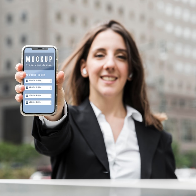スマートフォンのモックアップを保持している女性の正面図
