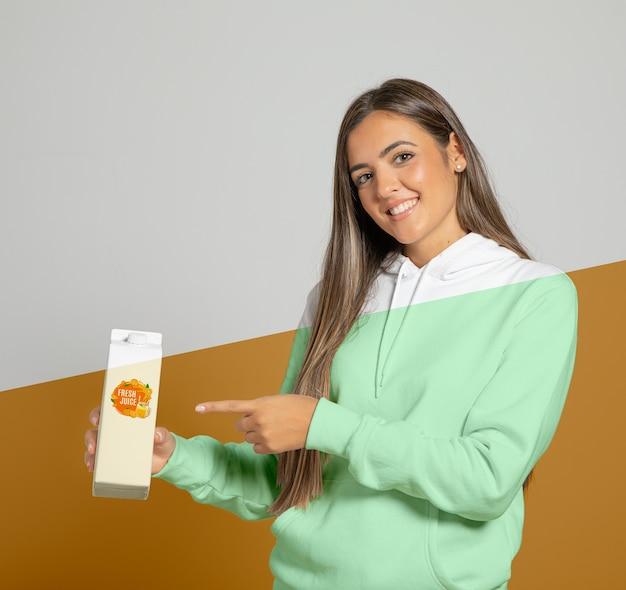 Вид спереди женщины в толстовке с капюшоном, указывая на коробку сока