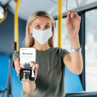 스마트 폰 들고 버스에서 의료 마스크를 가진 여자의 전면보기