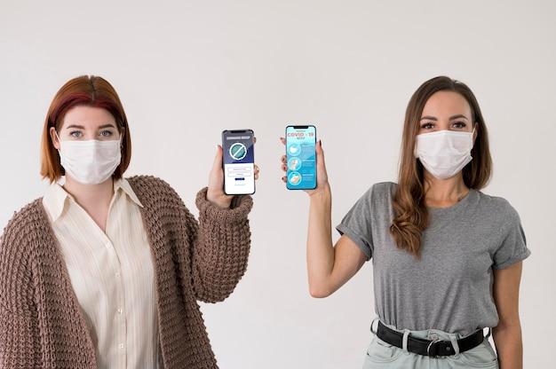 Вид спереди женщин в масках, держащих смартфоны