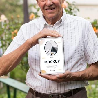 Vista frontale del vecchio uomo che tiene un tablet mock-up