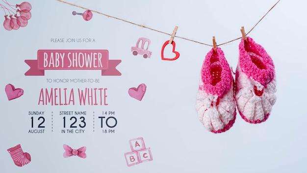 Vista frontale di scarpe rosa e invito per baby shower