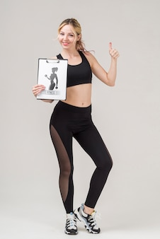 Front view of smiley fitness woman holding notepad and giving thumbs up