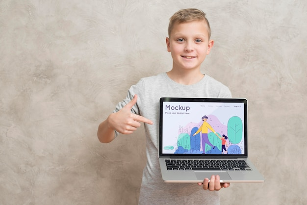 Front view of smiley kid holding and pointing at laptop