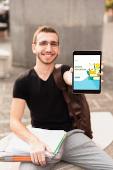 Front view student holding tablet