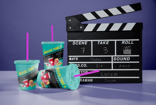 Front view of three cinema cups with straws and clapperboard