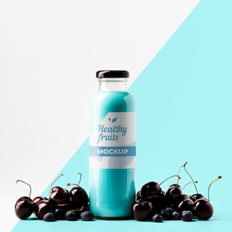 Front view of transparent juice bottle with cherries
