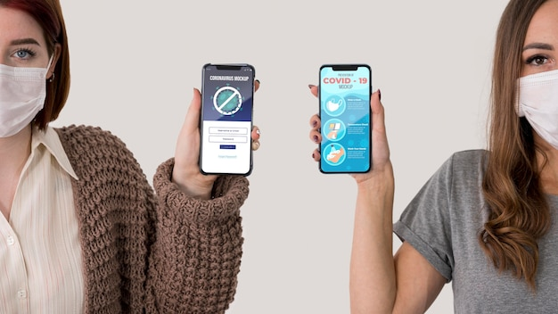 Vista frontale di due donne con maschere che tengono smartphone
