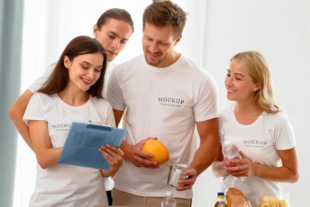 Vista frontale di volontari che controllano il blocco note con le donazioni