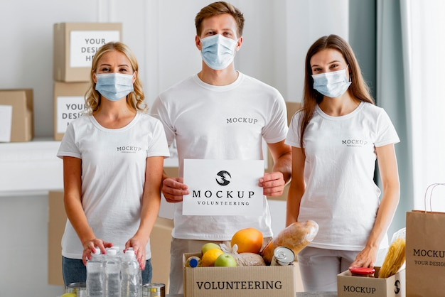 Front view of volunteers with medical masks holding blank paper next to food box