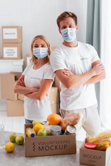 Vista frontale di volontari con maschere mediche in posa con scatole di donazione