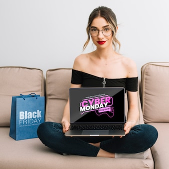 Front view of woman holding a laptop with cyber monday offer