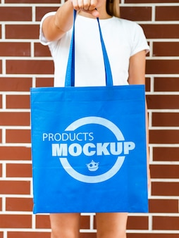 Front view woman holding a plain blue bag