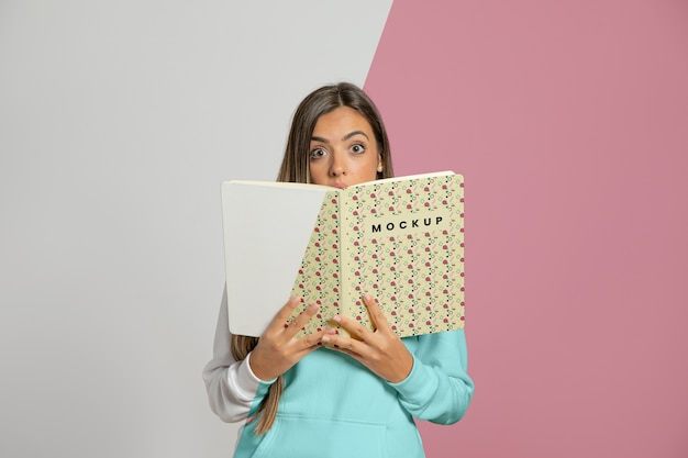 Front view of woman holding up book