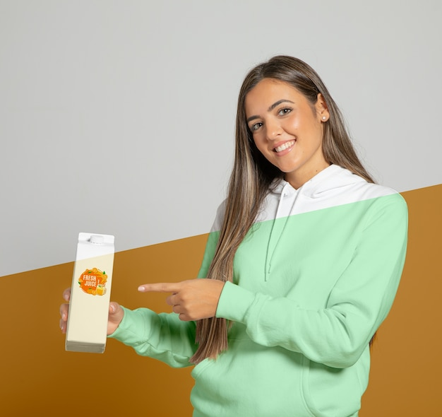 Front view of woman in hoodie pointing at juice carton