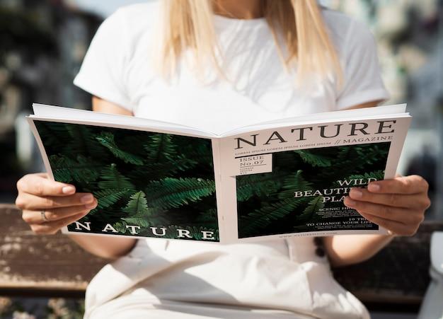 Женщина вид спереди, глядя в журнал природы