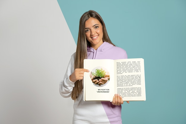 Front view of woman pointing at book she's holding