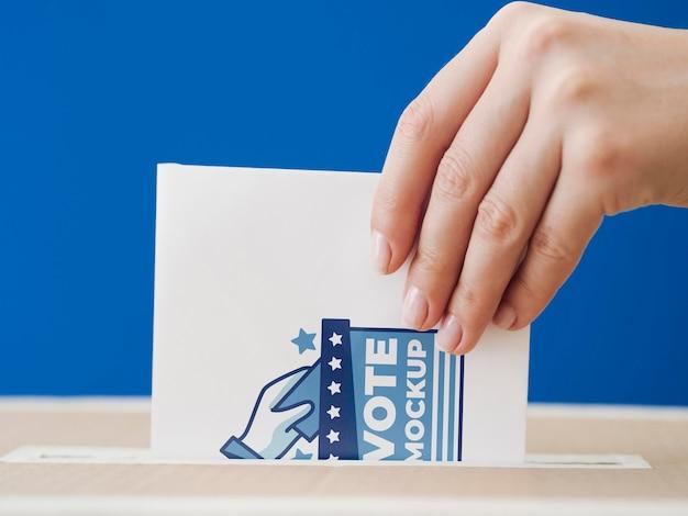 Donna di vista frontale che mette il modello di scheda elettorale nella casella