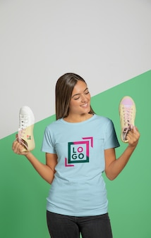 Front view of woman in t-shirt holding sneakers