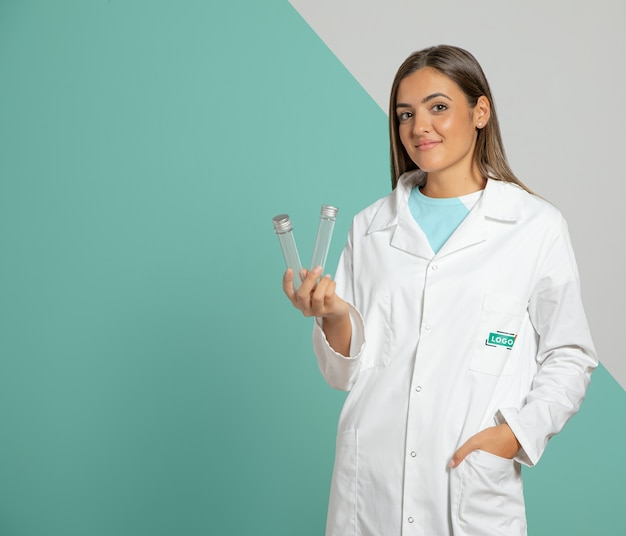 Front view of woman wearing lab coat and holding test tubes